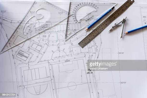 close-up of architect engineer drawing plan on blueprint with architect equipment - ontwerp stockfoto's en -beelden