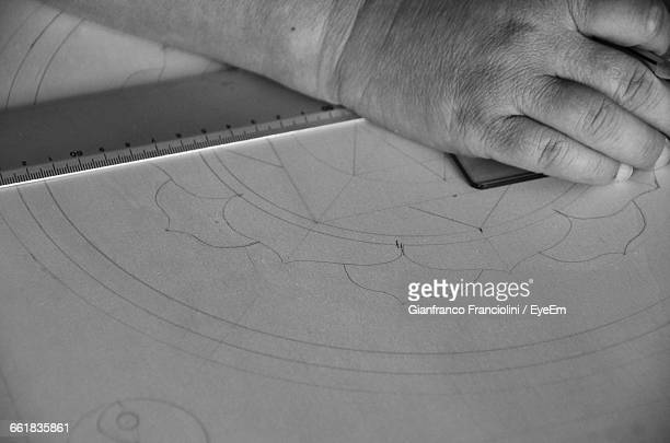 Close-Up Of Architects Hand Drawing On Paper