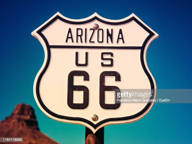 close-up of arizona 66 sign with number 66 against clear sky - route 66 stock-fotos und bilder