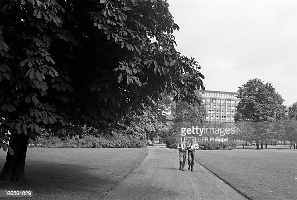 Close-Up Of Armin Hary. Cologne - septembre 1958 - L'athlète Armin HARY à droite, lisant son courrier en marchant dans une allée d'un parc, aux côtés...