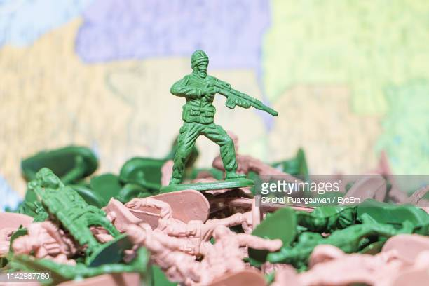 close-up of army soldier figurine aiming rifle - army soldier toy stock pictures, royalty-free photos & images