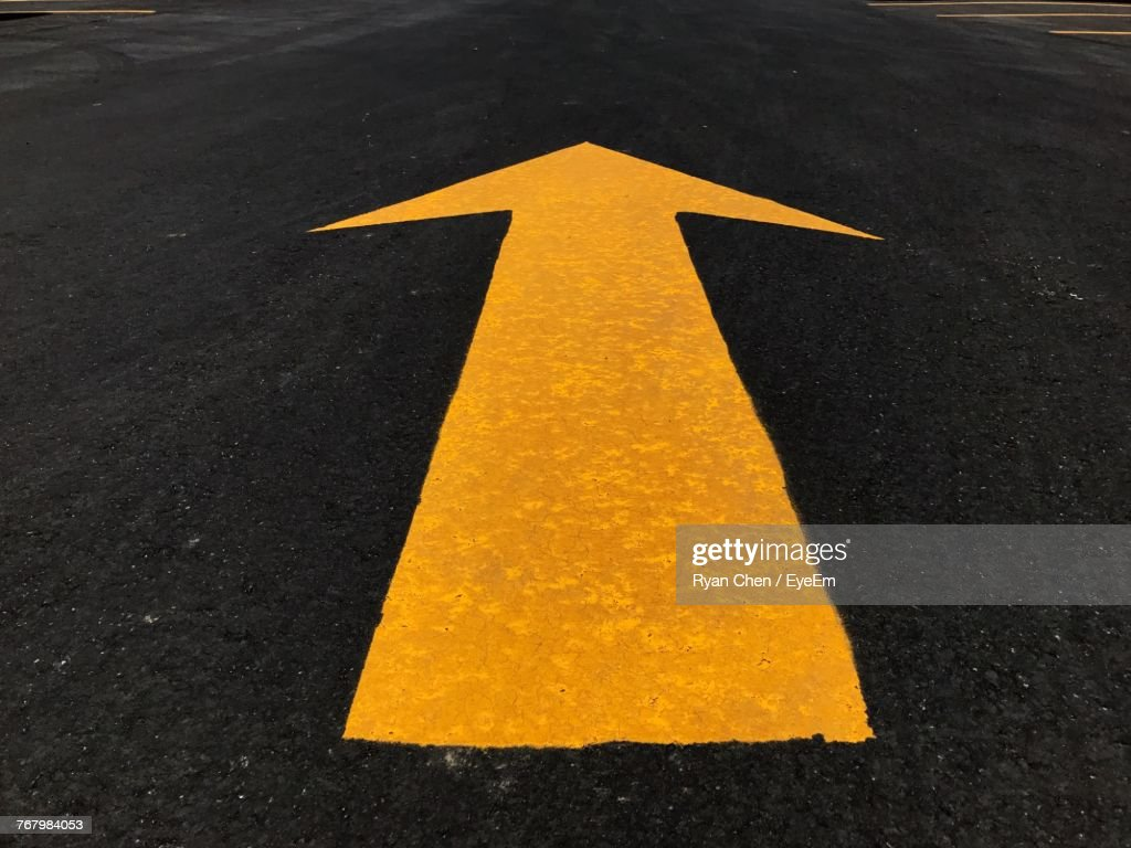 Close-Up Of Arrow Sign On Road : Stock Photo