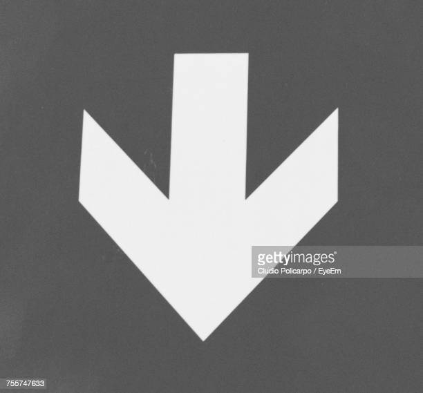 close-up of arrow symbol on gray background - chevron road sign stock pictures, royalty-free photos & images