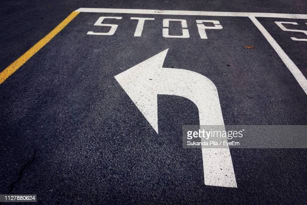 close-up of arrow symbol on road - curved arrows stock photos and pictures