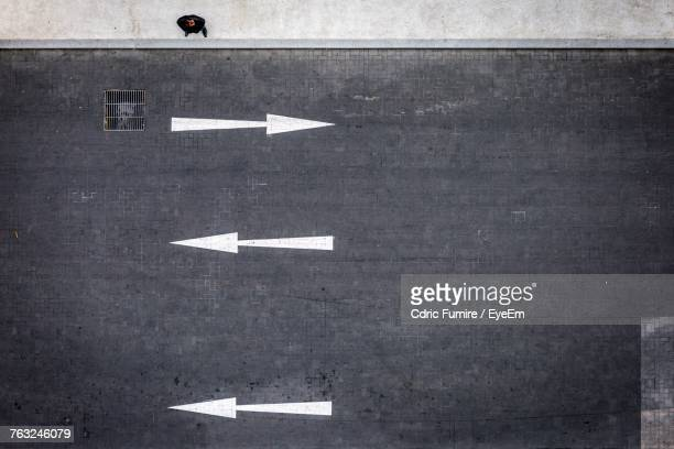 close-up of arrow symbol on road - one direction stock pictures, royalty-free photos & images