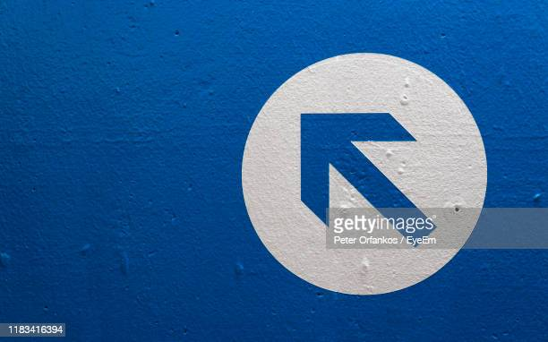 close-up of arrow symbol on wall - chevron road sign stock pictures, royalty-free photos & images