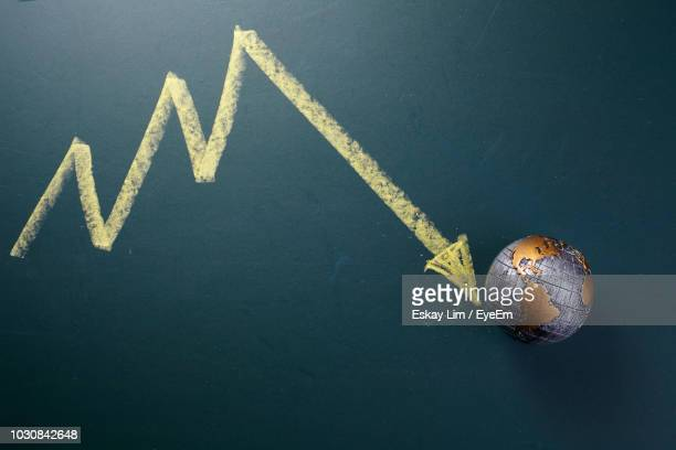 close-up of arrow symbol with globe on table - recession stock pictures, royalty-free photos & images