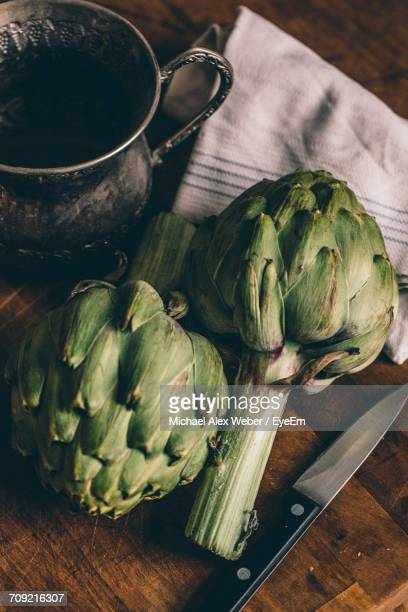 Close-Up Of Artichokes A Tin Pitcher And Knife On Cutting Board