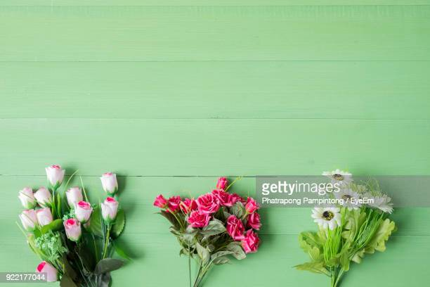 close-up of artificial flowers on table - green wood stock pictures, royalty-free photos & images