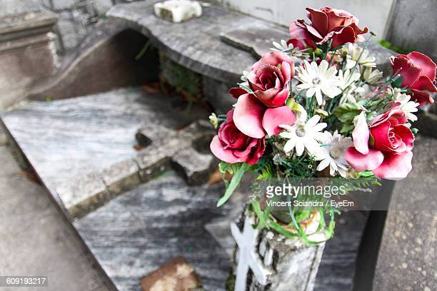 Close-Up Of Artificial Flowers On Tombstone At Cemetery