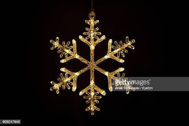 close-up of artificial illuminated snowflake against black background - snowflakes stock photos and pictures