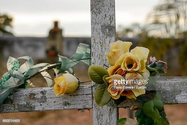 Close-Up Of Artificial Yellow Roses On Fence At Cemetery