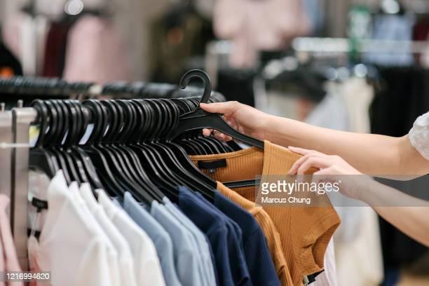 primo piani della mano femminile cinese asiatica che porta fuori un vestito al negozio di abbigliamento - abbigliamento foto e immagini stock