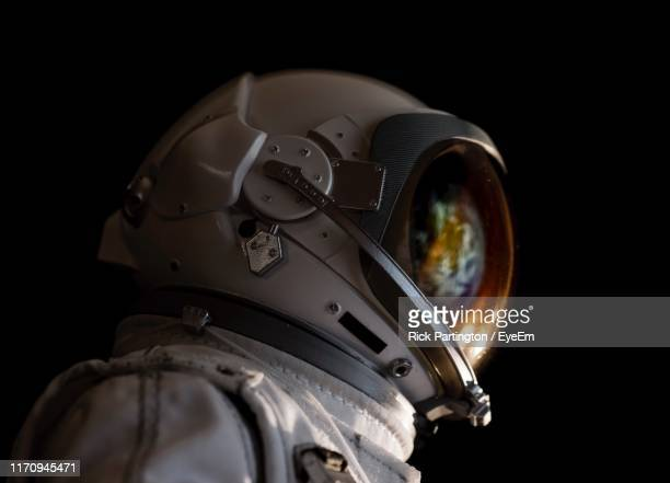 close-up of astronaut against black background - textfreiraum stock-fotos und bilder