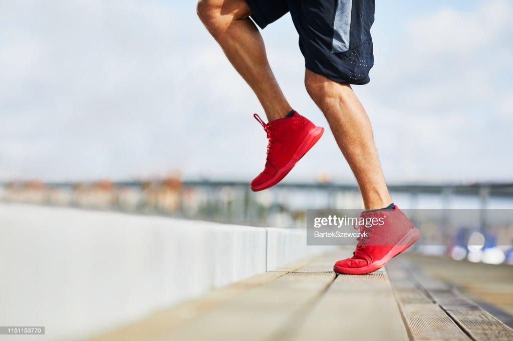 Closeup of athletic man doing HIIT workout outdoors : Stock Photo