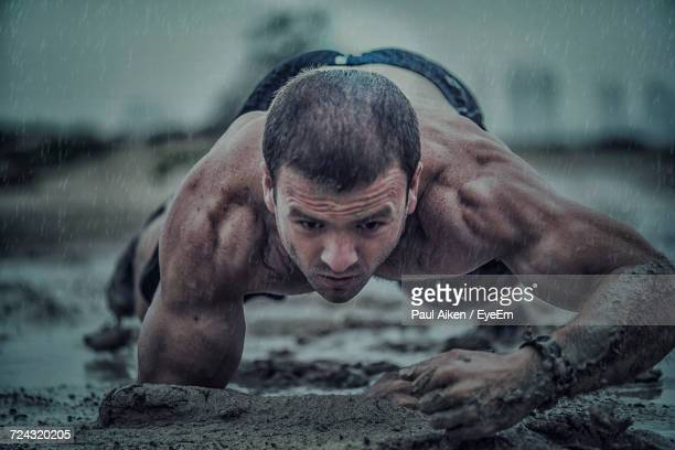close-up of athletic man exercising in mud during rainy season - aikāne stock pictures, royalty-free photos & images