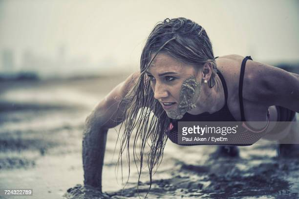 close-up of athletic woman exercising in mud - aikāne stock pictures, royalty-free photos & images