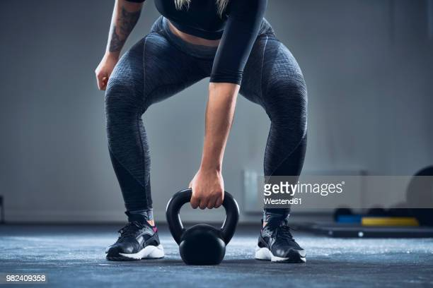 close-up of athletic woman exercising with kettlebell at gym - weight stock pictures, royalty-free photos & images