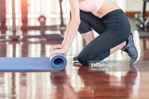 close-up of attractive young asian woman folding blue yoga or fitness mat after working out at yoga class in sport club. - gummihose stock-fotos und bilder