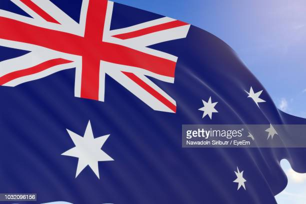 close-up of australian flag against blue sky - australian flag stock pictures, royalty-free photos & images