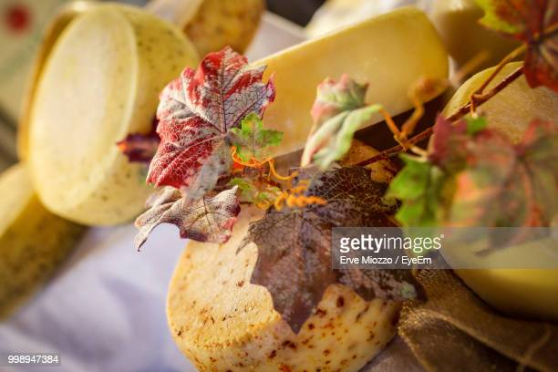 Close-Up Of Autumn Leaves With Cheese On Table