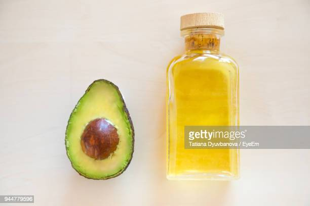 Close-Up Of Avocado And Oil Bottle On Table