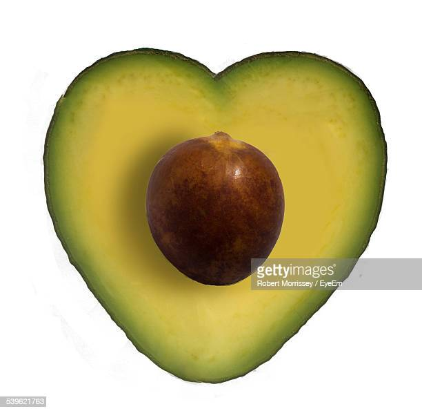 Close-Up Of Avocado Cut In Heart Shape Against White Background