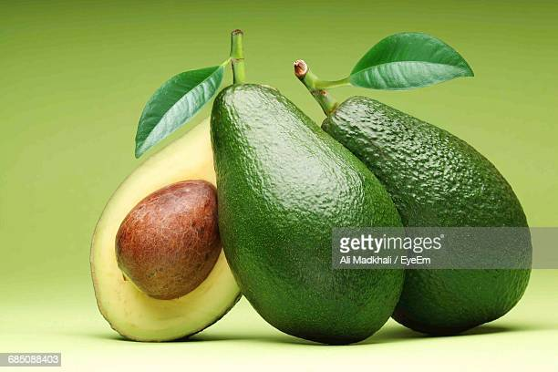 Close-Up Of Avocados Against Green Background