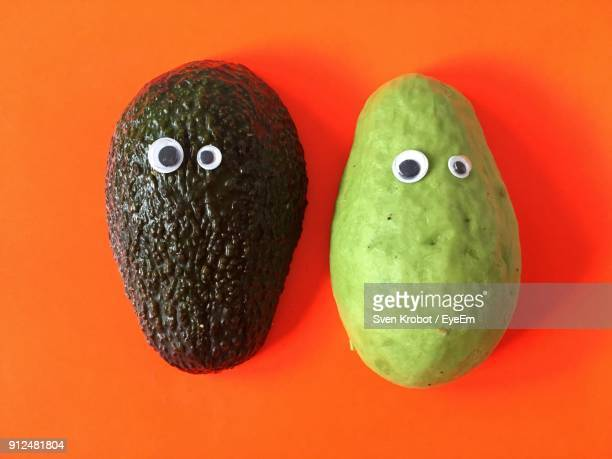 Close-Up Of Avocados Against Orange Background