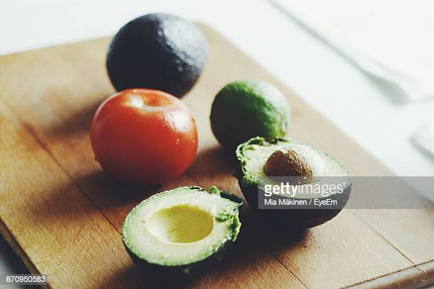 Close-Up Of Avocados And Tomato With Lime On Cutting Board