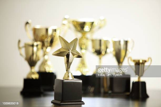 close-up of awards on table against wall - award stock pictures, royalty-free photos & images