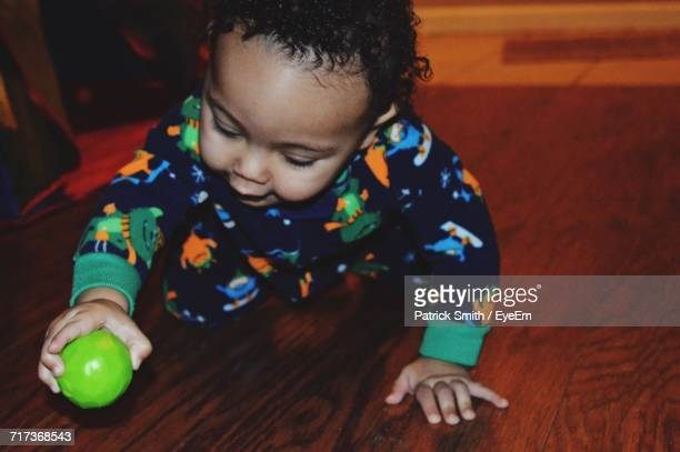 Close-Up Of Baby Boy Playing With Ball On Hardwood Floor