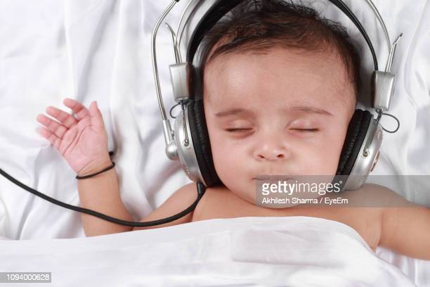close-up of baby boy wearing headphones while sleeping on bed - babyhood stock pictures, royalty-free photos & images