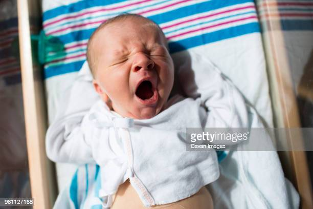 Close-up of baby boy yawning while sleeping in crib at hospital