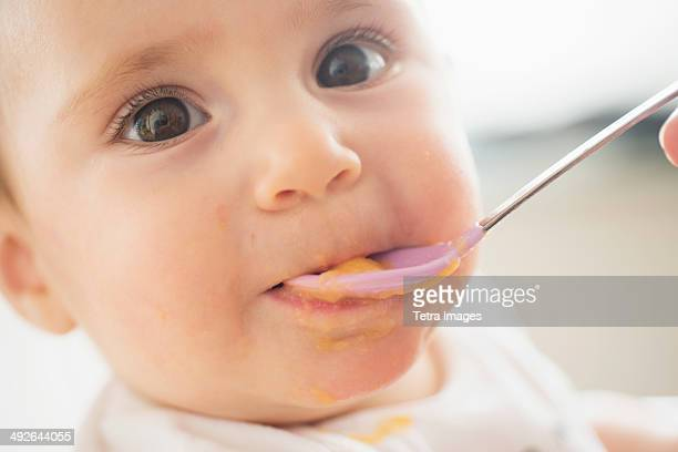 Close-up of baby girl (12-17 months) being spoon fed, Jersey City, New Jersey, USA