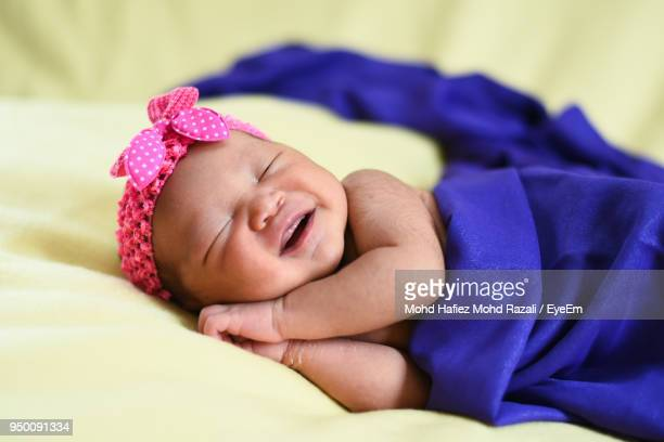 Close-Up Of Baby Girl Sleeping On Bed At Home