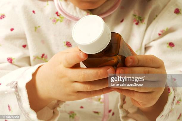 Closeup of baby girl trying to open medicine bottle mid section