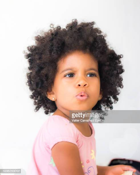 close-up of baby girl with curly black hair against white wall - cabelo preto - fotografias e filmes do acervo