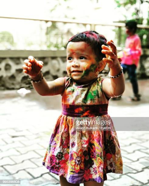 Close-Up Of Baby Girl With Face Paint On Footpath During Holi