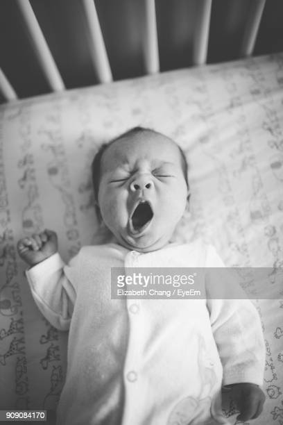 close-up of baby girl yawning in crib - babyhood stock pictures, royalty-free photos & images