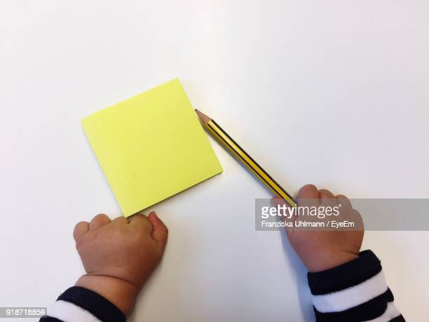 Close-Up Of Baby Hand Holding Pencil By Adhesive Notes Against White Background