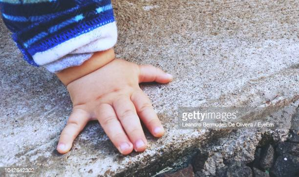 Close-Up Of Baby Hand On Rock