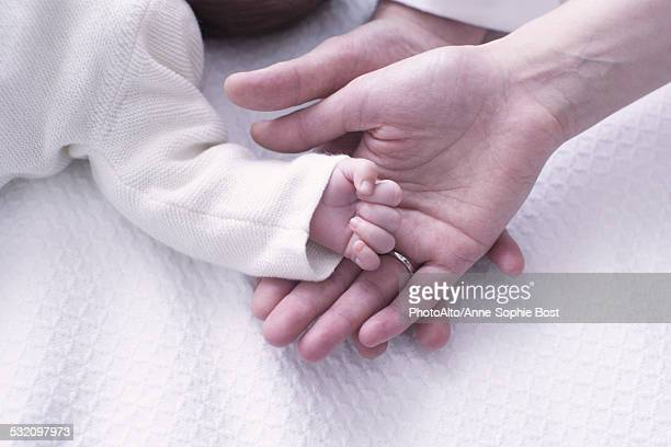 Close-up of babys hand resting on parents hands