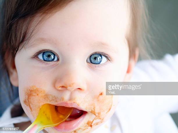 Close-up of baby's messy face and spoon