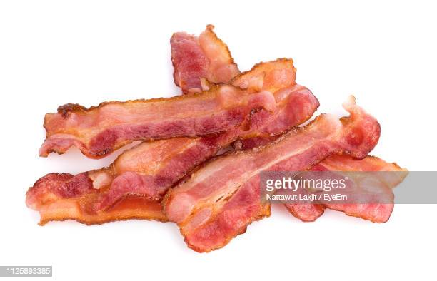 Close-Up Of Bacon Against White Background