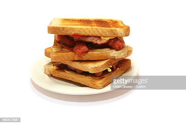 Close-Up Of Bacon Sandwich Served In Plate Against White Background