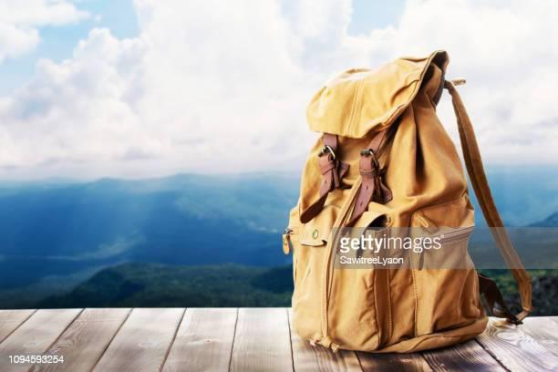 close-up of bag on wood against sky - rucksack stock-fotos und bilder