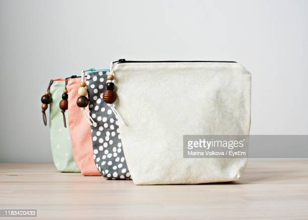 close-up of bags on table against white background - white purse stock pictures, royalty-free photos & images
