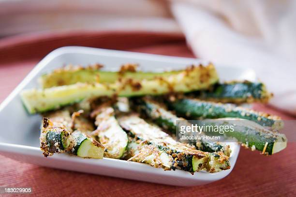 Close-up of baked zucchini fries on white plate