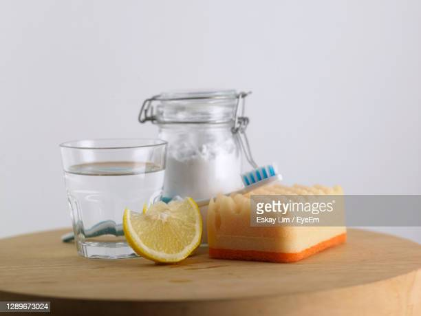 close-up of baking soda in glass jar vinegar and lemon on table - cleaning agent stock pictures, royalty-free photos & images